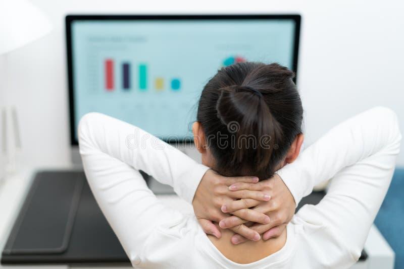 Ung affärskvinna som tänker, medan arbeta på den skrivbords- datoren på den moderna inrikesdepartementet royaltyfri foto
