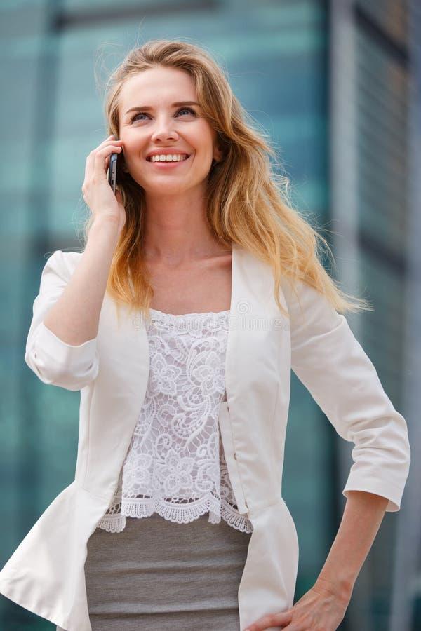Ung affärskvinna som talar på mobiltelefonen, medan gå som är utomhus- arkivbild