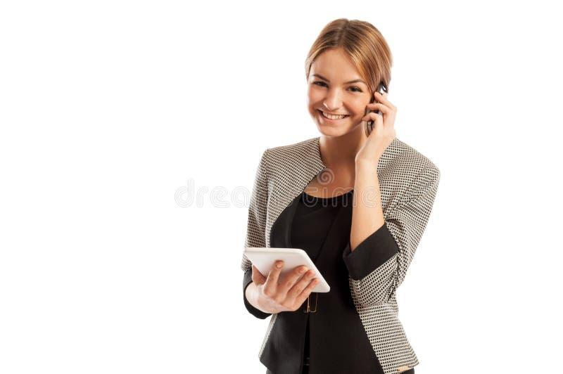 Ung affärskvinna som talar på telefon- och innehavminnestavlan royaltyfri fotografi