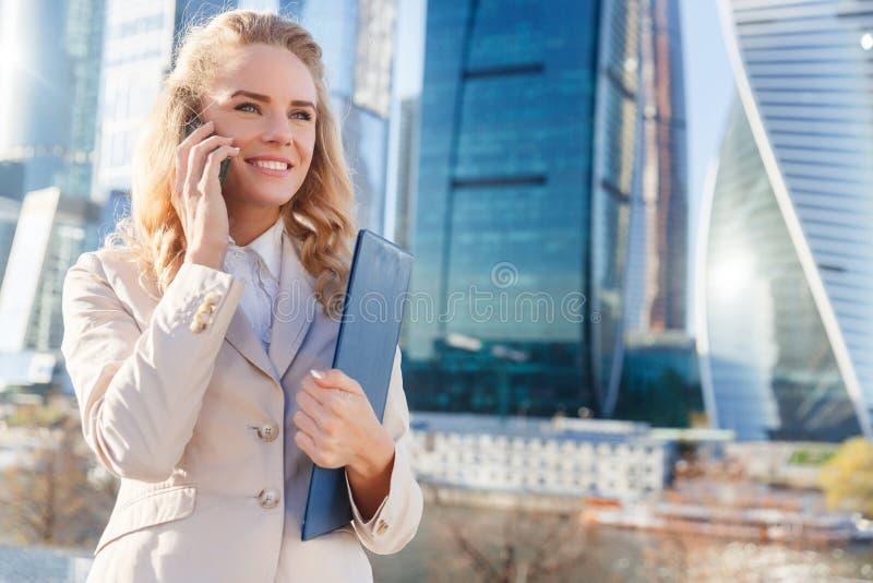 Ung affärskvinna som talar på telefonen nära modern kontorsbyggnad royaltyfri bild