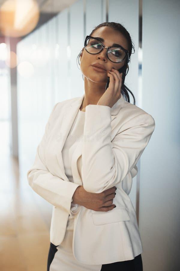 Ung affärskvinna som talar vid mobiltelefonen i ljust modernt kontor fotografering för bildbyråer