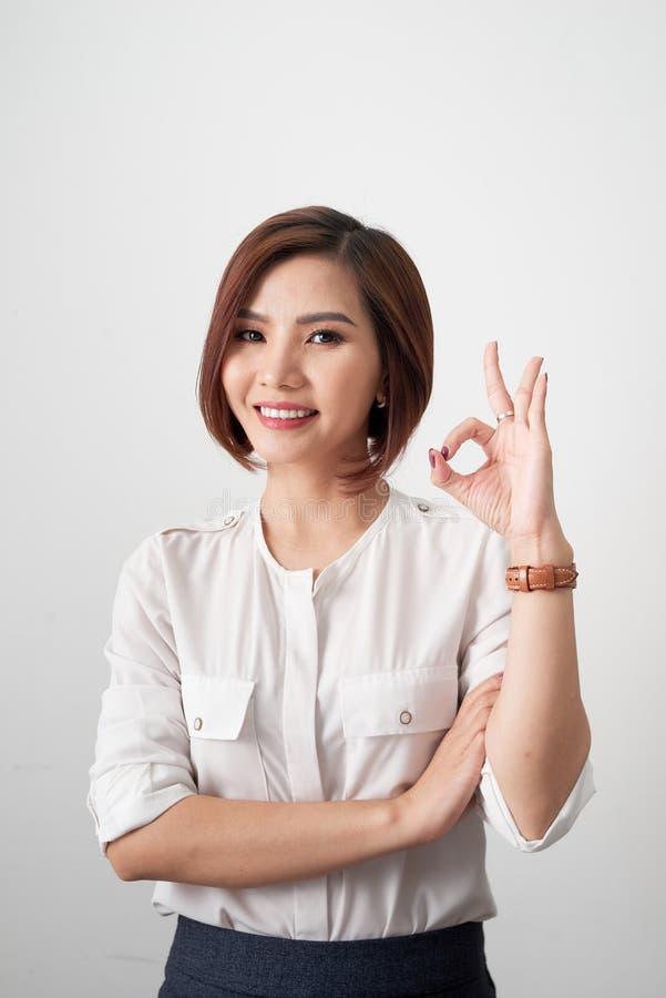 Ung affärskvinna som visar det reko tecknet på vit bakgrund royaltyfri foto
