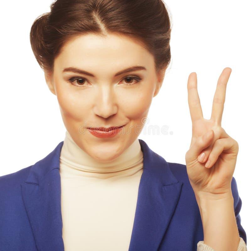 Ung affärskvinna som visar ett segertecken I arkivbild