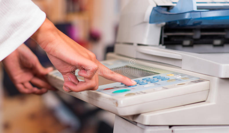 Ung affärskvinna Using Copy Machine på kontoret royaltyfri foto
