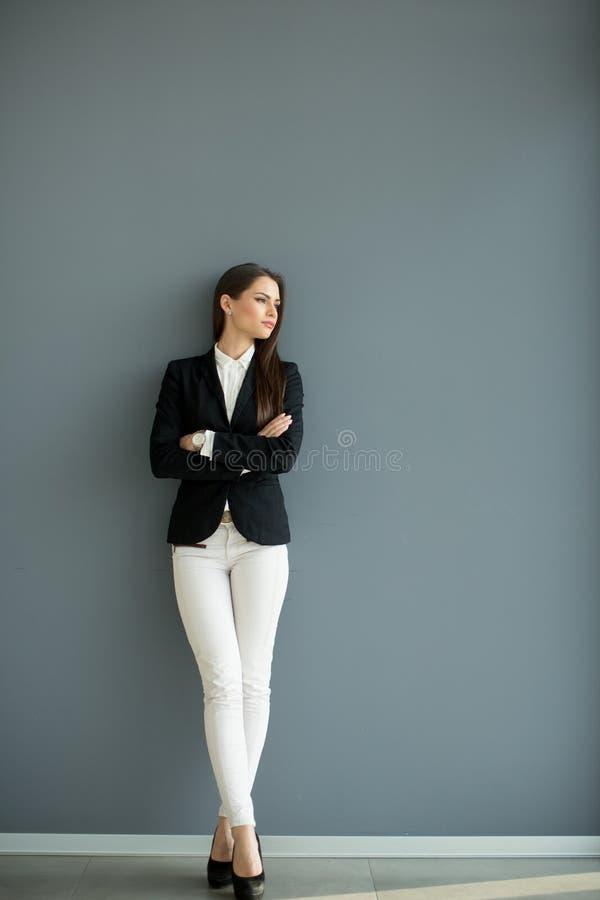 Ung affärskvinna vid väggen royaltyfri foto