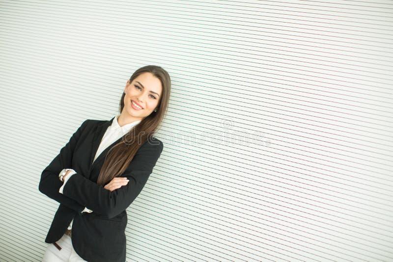 Ung affärskvinna vid väggen arkivfoto