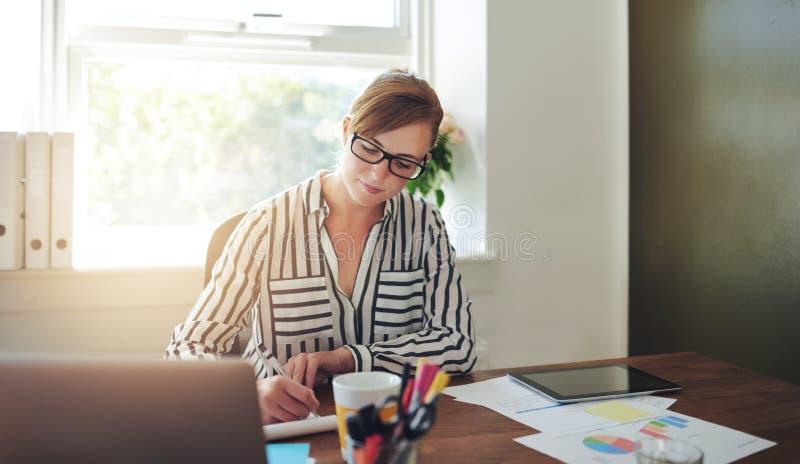 Ung affärskvinna Writing Notes på hennes skrivbord arkivfoton