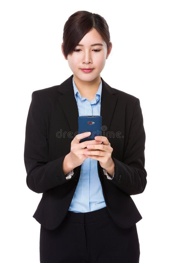 Ung affärskvinnakontrollemail på den smarta telefonen royaltyfri foto