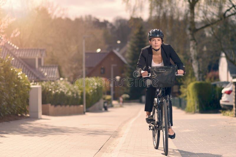 Ung affärskvinnaridning som arbetar på en cykel royaltyfri fotografi