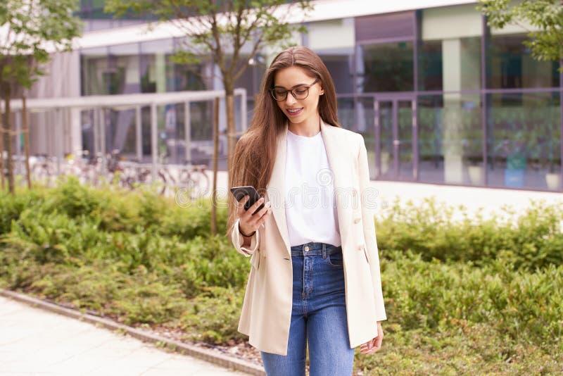 Ung affärskvinnatextmessaging, medan gå på gatan i staden arkivfoton