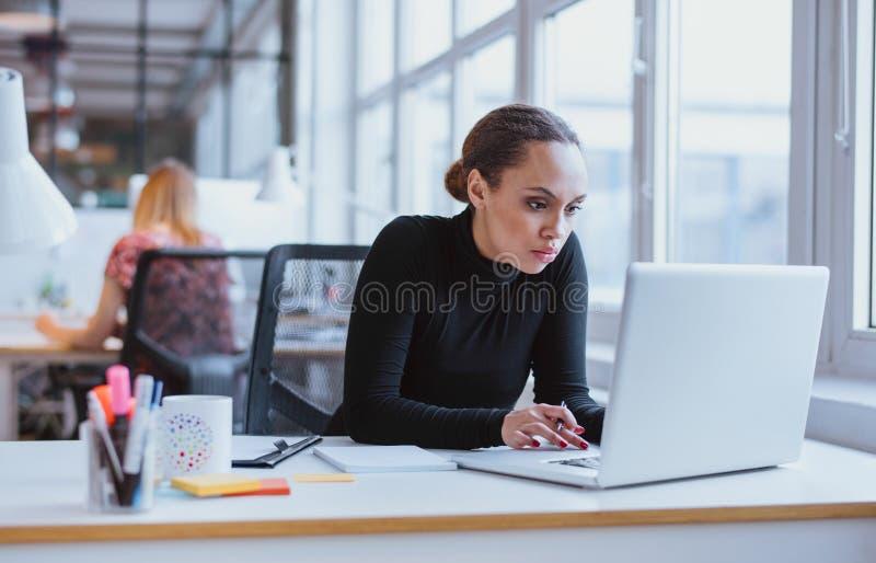 Ung affärsledare som använder bärbara datorn royaltyfri foto