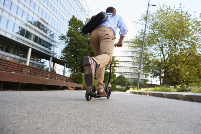 Ung affärsman Commuting To Work till och med stad på sparkcykeln fotografering för bildbyråer