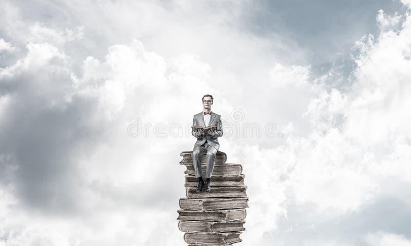 Ung affärsman eller student som flyter i blå himmel och studerar vetenskapen royaltyfria foton