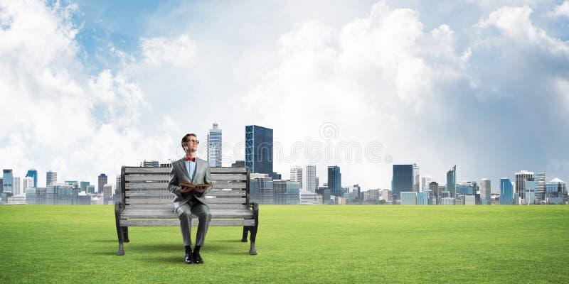 Ung affärsman eller student som studerar vetenskapen och cityscapen på bakgrund royaltyfri bild