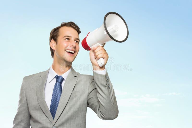 Ung affärsman i dräkt med en megafon i hans hand som ler arkivfoton