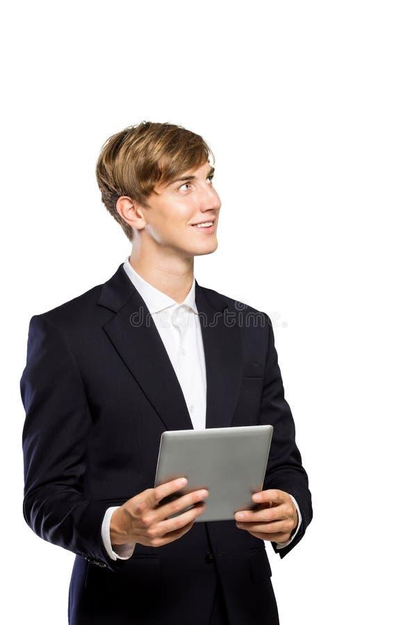 Ung affärsman i dräkt med en minnestavlaPC på hans hand som ser arkivbilder