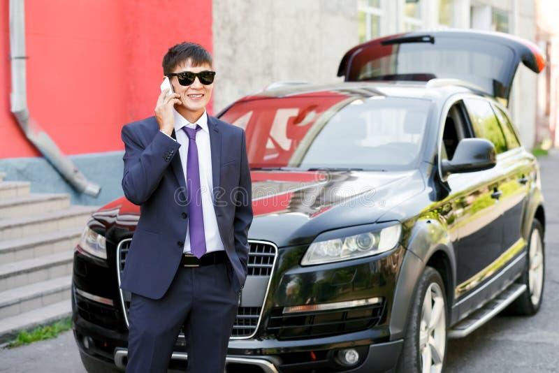 Ung affärsman i dräkt och solglasögon som talar på telefonen bredvid den dyra bilen, utomhus royaltyfri foto