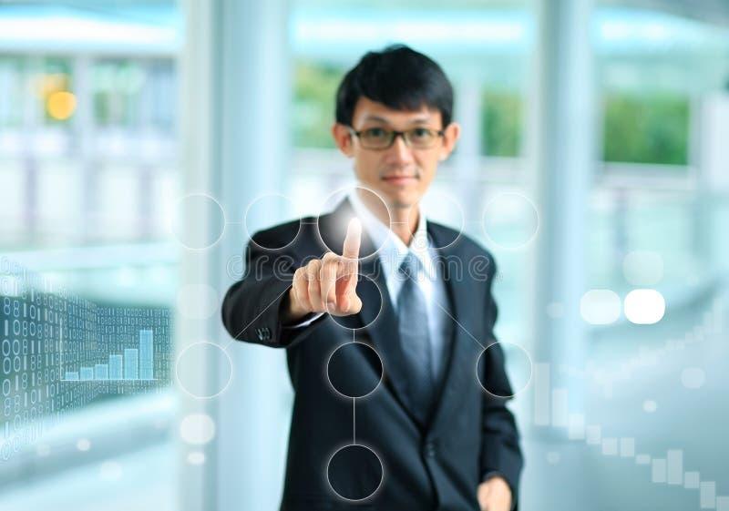 Ung affärsman i en dräkt som pekar med hans finger för att trycka på s royaltyfri bild