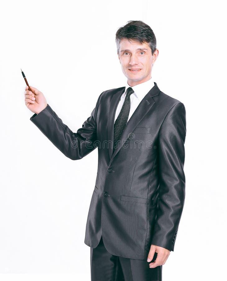 Ung affärsman i en dräkt som pekar med en penna på vit bakgrund royaltyfri fotografi