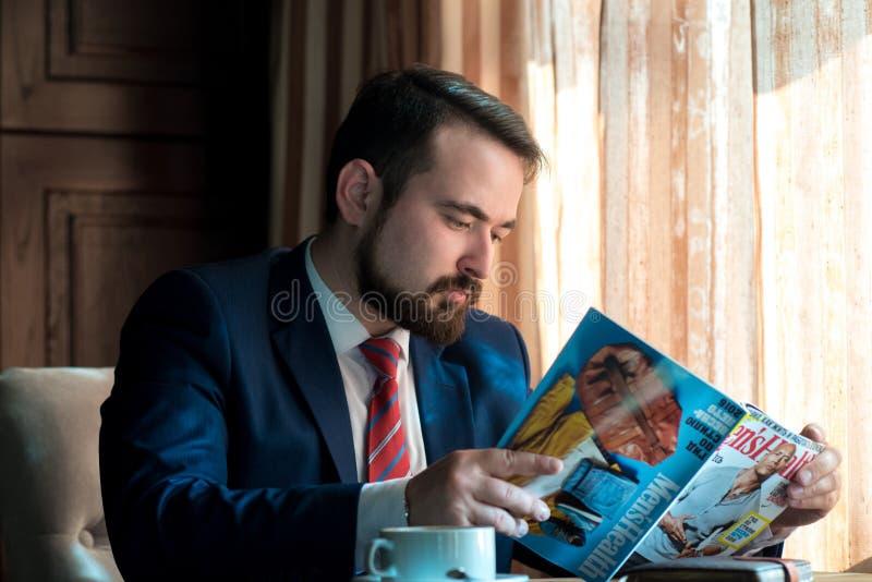 Ung affärsman i en läs- tidskrift för kafé royaltyfria bilder