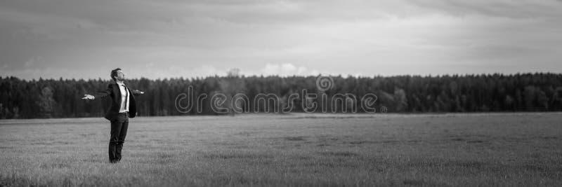 Ung affärsman i ett dräktanseende i en äng med hans öppna armar vitt arkivbild