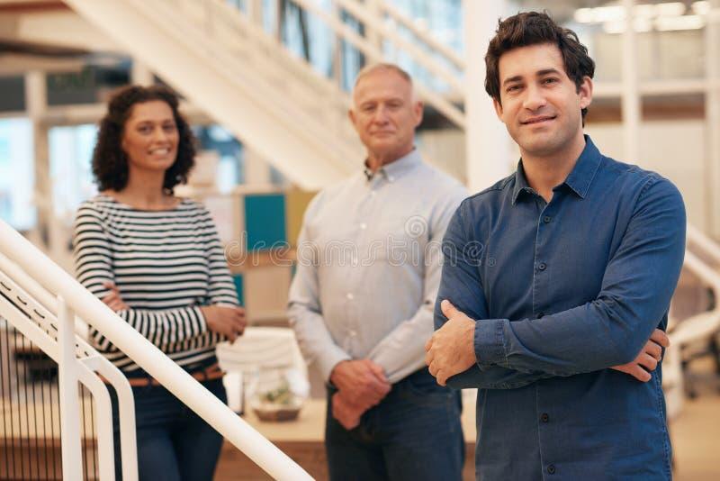 Ung affärsman i ett kontor med coworkers som står bak honom fotografering för bildbyråer