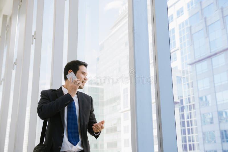 Ung affärsman i flygplats Tillfällig stads- yrkesmässig affärsman som använder smartphonen som ler lycklig inre kontorsbyggnad arkivfoton
