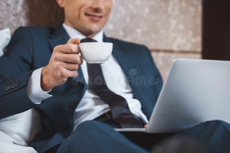 Ung affärsman i formell dräkt genom att använda hans bärbar dator- och innehavkopp kaffe, medan sitta på säng arkivbild