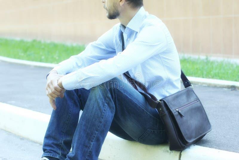 Ung affärsman i tillfällig kläder med sitti för kort påse för läder arkivfoton