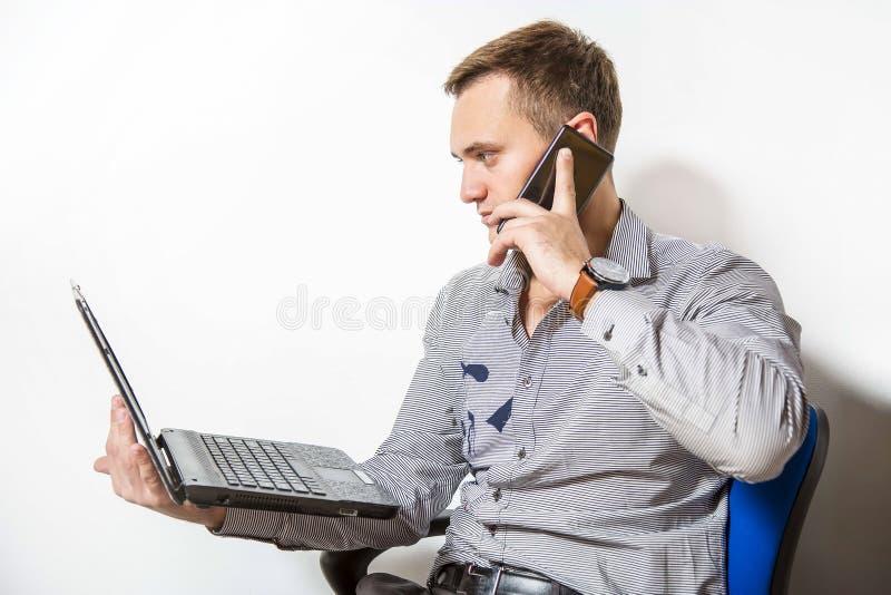 Ung affärsman med bärbara datorn och telefonen Han ser skärmen och talar hänsynsfullt på mobilen fotografering för bildbyråer
