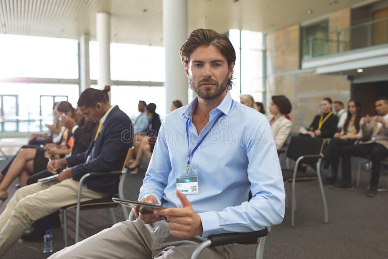 Ung affärsman med den digitala minnestavlan som ser kameran under seminarium royaltyfri bild