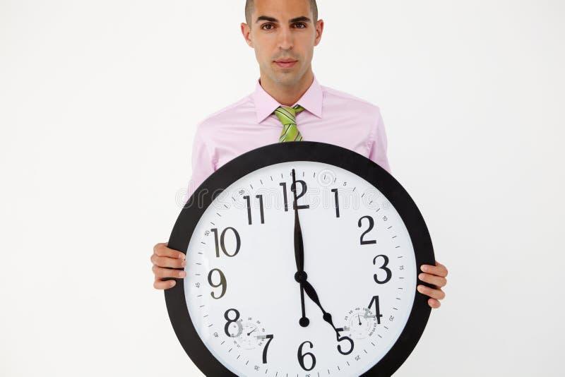 Ung affärsman med den jätte- klockan arkivbild