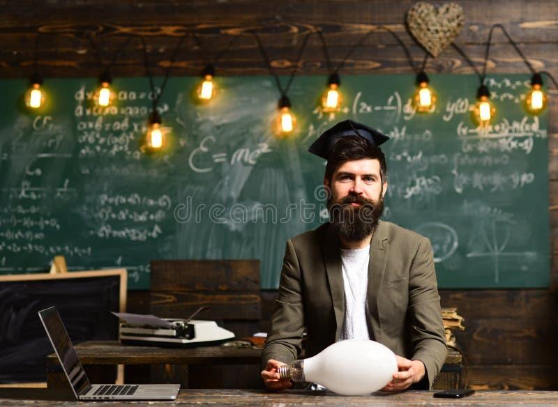 Ung affärsman med dräkten och att tänka för skägg den bärande Svart tavlabakgrund med många tända lightbulbs Begrepp av tvivel arkivbild
