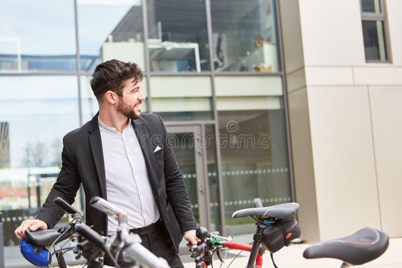 Ung affärsman med en cykel royaltyfri fotografi