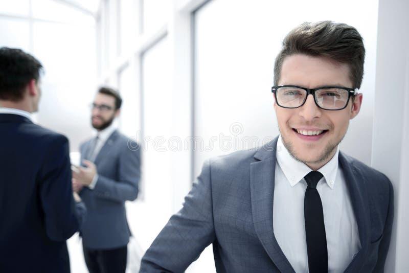 Ung affärsman med exponeringsglas som står i hallkontoret arkivbilder