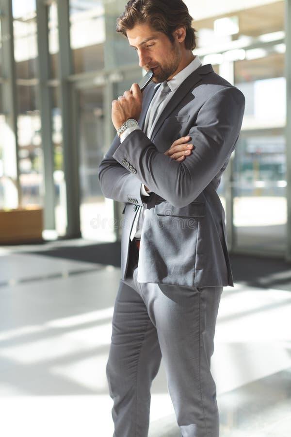 Ung affärsman med huvudet ner med hans mobiltelefonanseende i lobbykontor royaltyfria foton