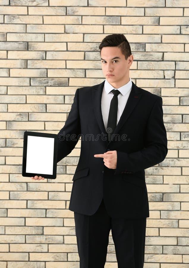 Ung affärsman med minnestavladatoren mot tegelstenväggen arkivbild
