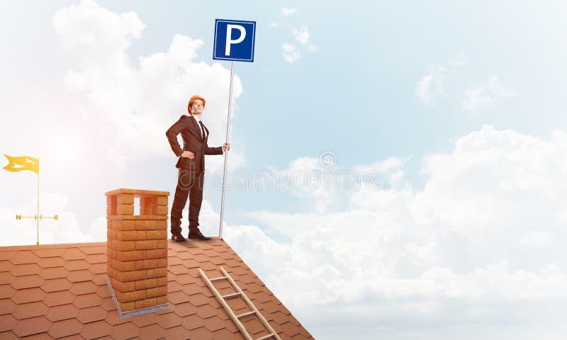Ung affärsman med parkeringsteckenanseende på tegelstentaket Blandat massmedia fotografering för bildbyråer