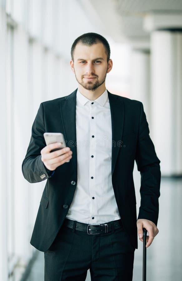 Ung affärsman med resväskan och att använda väntande på flyg för smart telefon Caucasian affärsman som väntar på holdin för flygp royaltyfria bilder