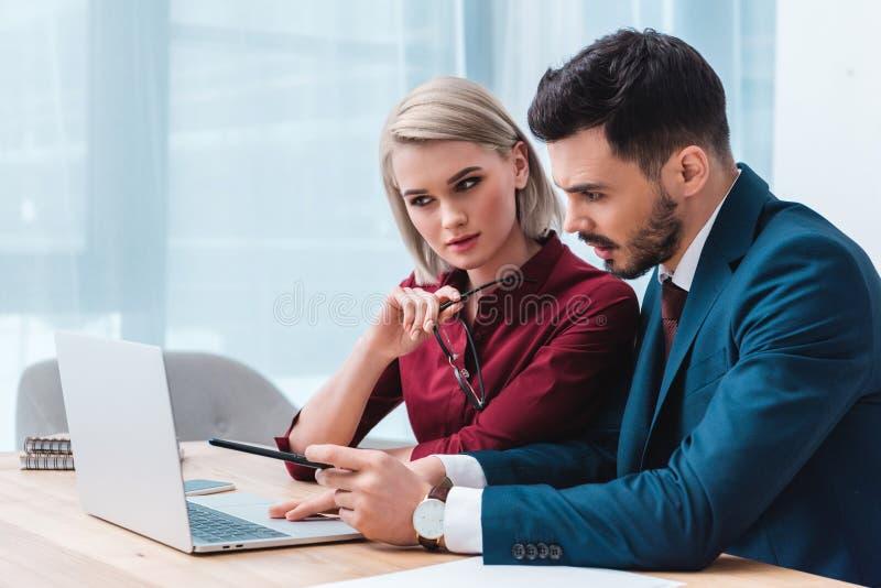 ung affärsman och affärskvinna som tillsammans arbetar och använder bärbara datorn royaltyfri fotografi