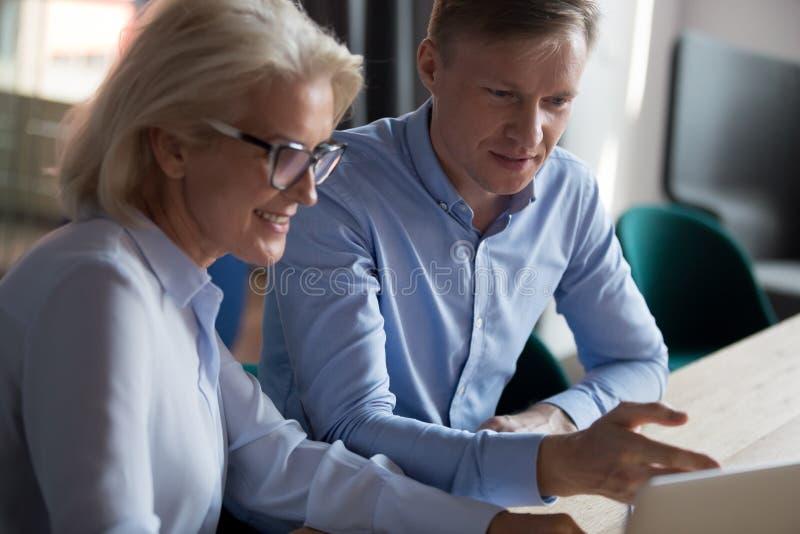Ung affärsman och mogen kvinna som tillsammans arbetar på datorprojekt royaltyfria bilder