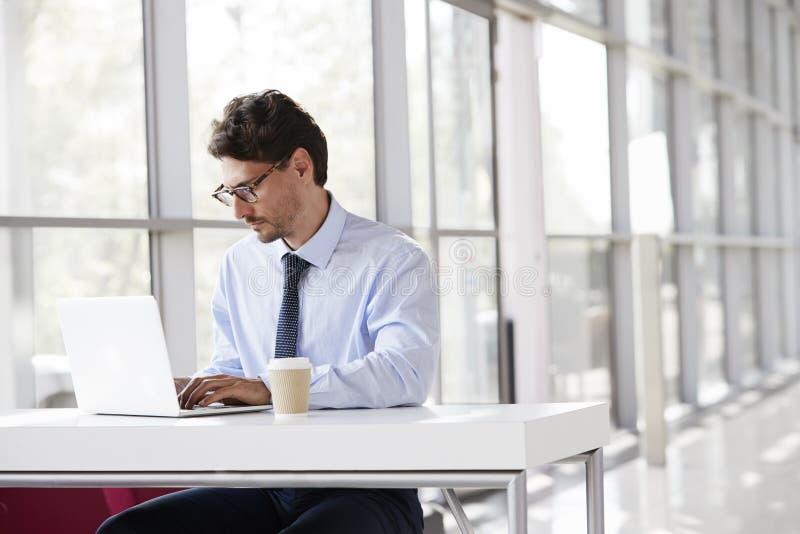 Ung affärsman på ett skrivbord som arbetar på hans bärbar dator arkivbilder