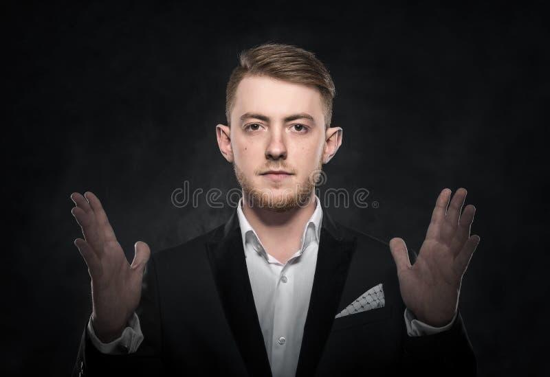 Ung affärsman på mörk bakgrund royaltyfri fotografi