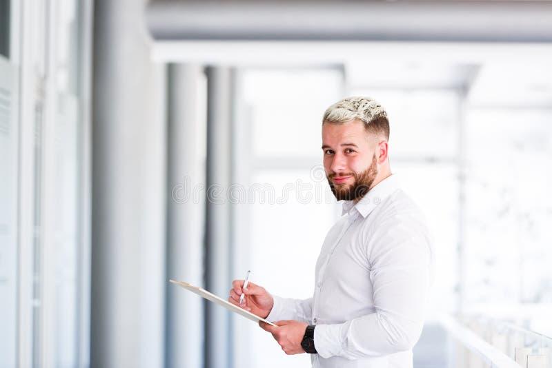 Ung affärsman Posing While Writting på någon skrivbordsarbete arkivfoton