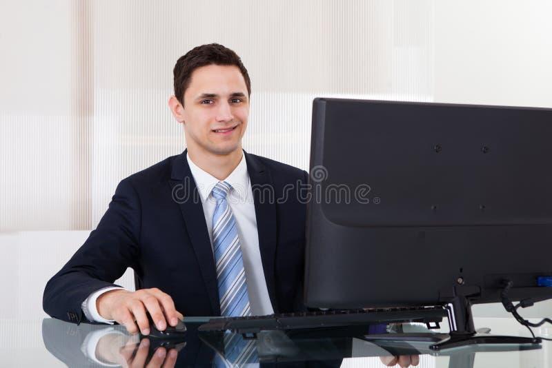 Ung affärsman som använder datoren på kontorsskrivbordet royaltyfria foton