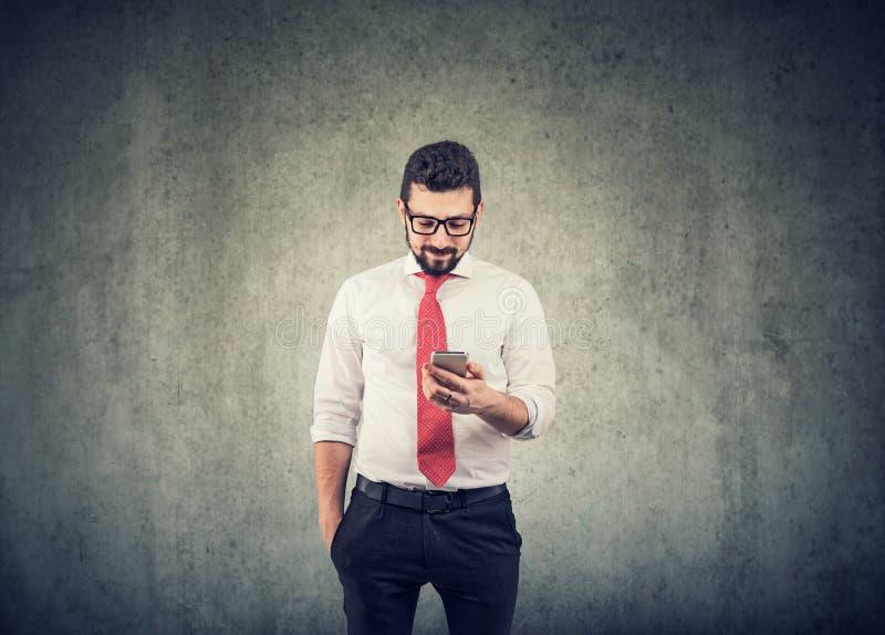 Ung affärsman som använder en mobil telefon royaltyfri foto