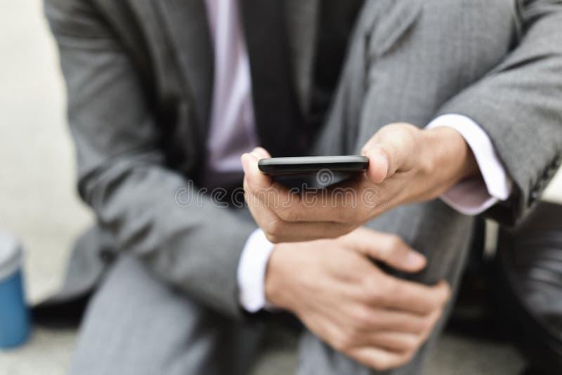 Ung affärsman som använder en smartphone arkivbild