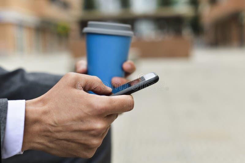 Ung affärsman som använder en smartphone royaltyfri foto