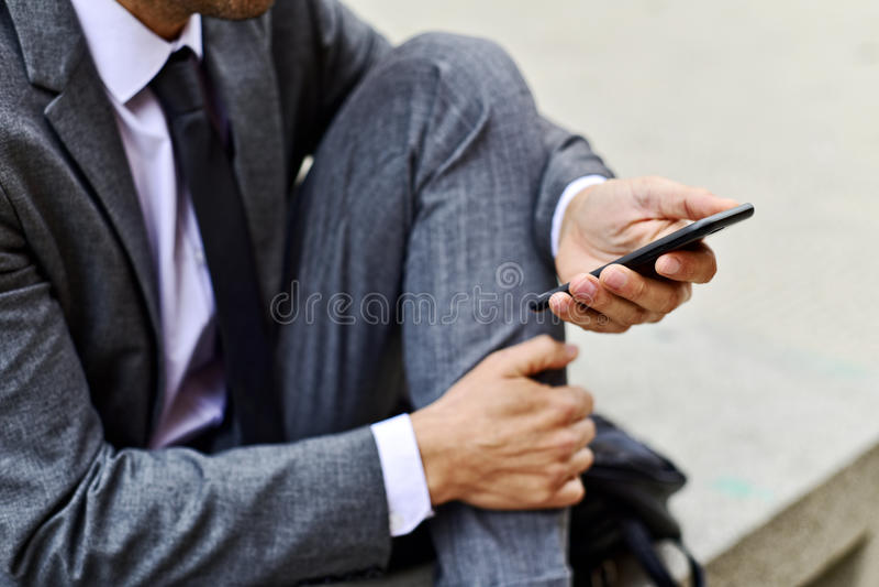 Ung affärsman som använder en smartphone royaltyfria bilder