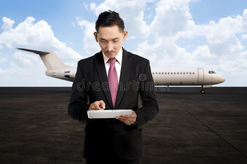 Ung affärsman som använder hans minnestavla på flygplatsen arkivbilder